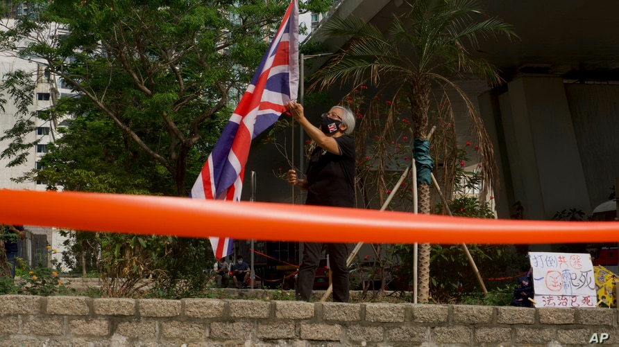 A pro-democracy supporter holds a British flag outside a court in Hong Kong Thursday, April 1, 2021. Seven pro-democracy…