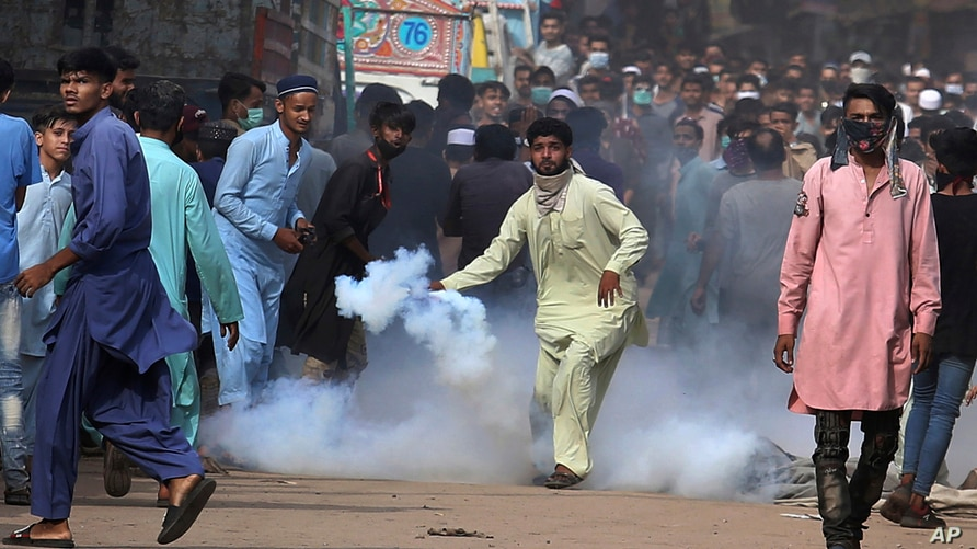 A supporters of Tehreek-e-Labiak Pakistan, a banned Islamist party, prepares to hurl back a tear gas canister fired by police…