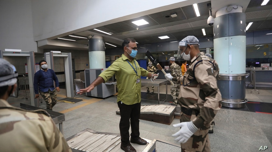 An Indian paramilitary soldier wearing protective gear frisks journalists during a press preview to show the preparedness of…
