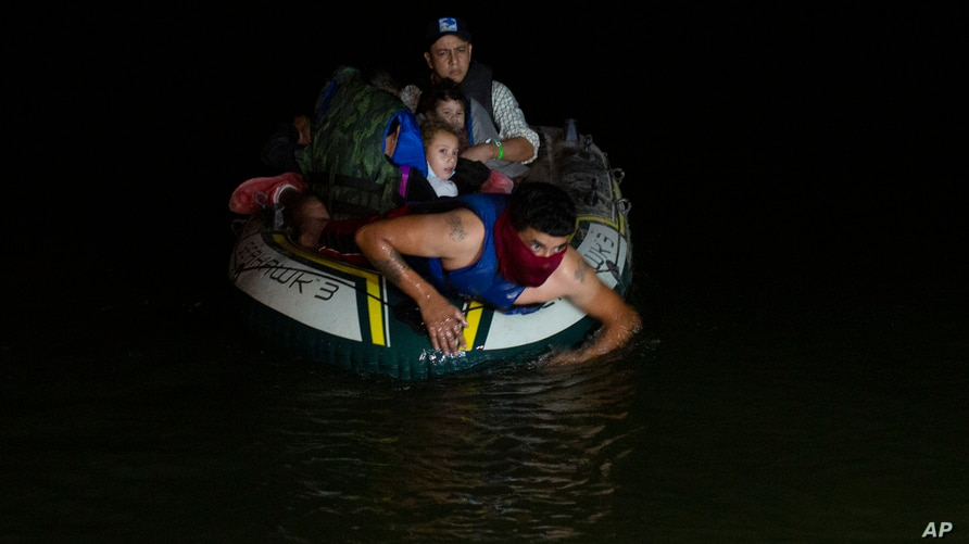 A smuggler takes migrants, mostly from Central American countries, on a small inflatable raft towards U.S. soil in Roma, Texas…