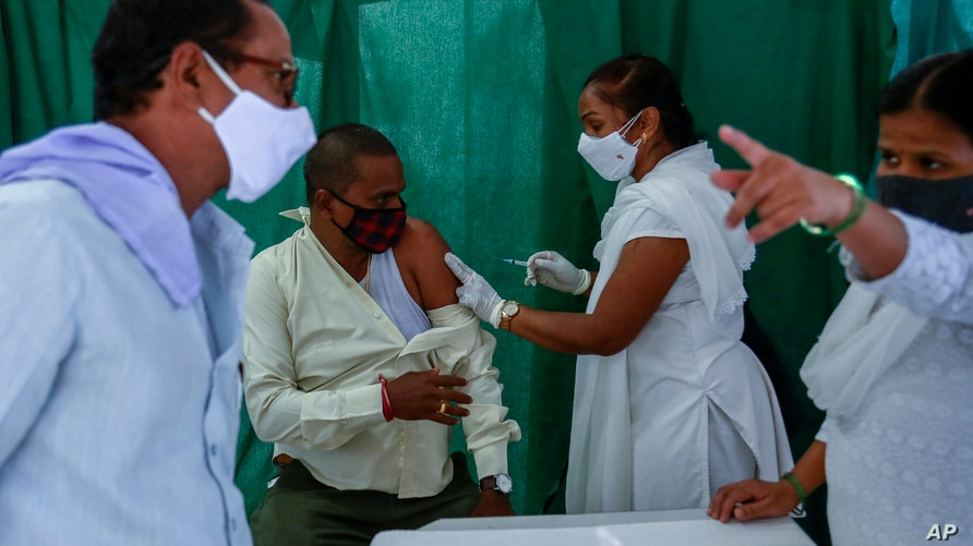 People wear masks as a precaution against the coronavirus as a health worker administers the COVISHIELD vaccine at a government…