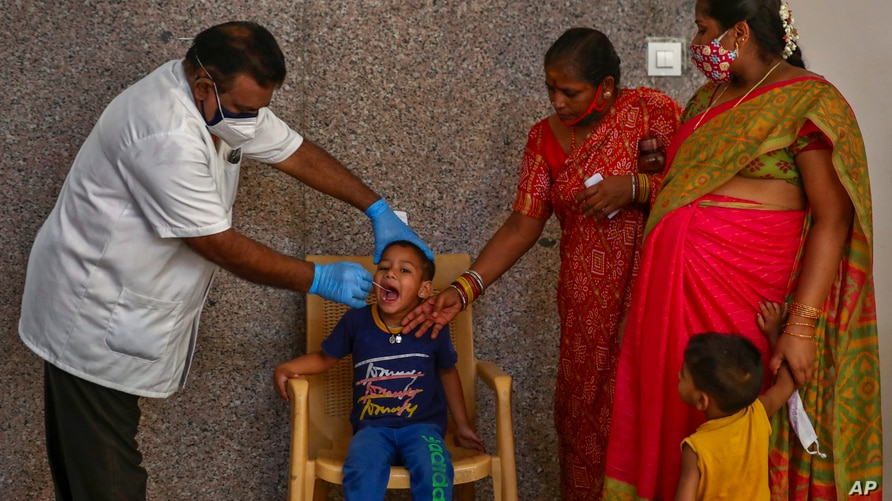 A health worker takes a mouth swab sample of a boy to test for COVID-19 in Hyderabad, India, Thursday, April 29, 2021. (AP…