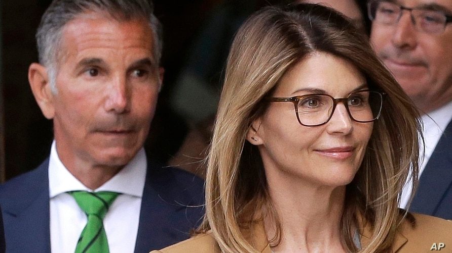 FILE - In this April 3, 2019, file photo, actress Lori Loughlin, front, and her husband, clothing designer Mossimo Giannulli,…