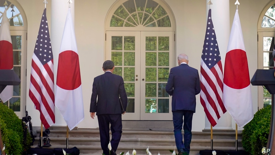 President Joe Biden and Japanese Prime Minister Yoshihide Suga leave after a news conference in the Rose Garden of the White…