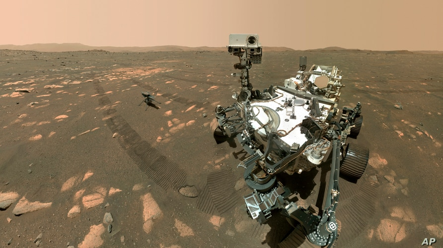 This Tuesday, April 6, 2021 image made available by NASA shows the Perseverance Mars rover, foreground, and the Ingenuity…