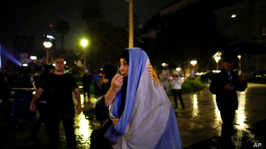 A woman protests the new measures announced to stop the spread of COVID-19, outside the government house in Buenos Aires,…