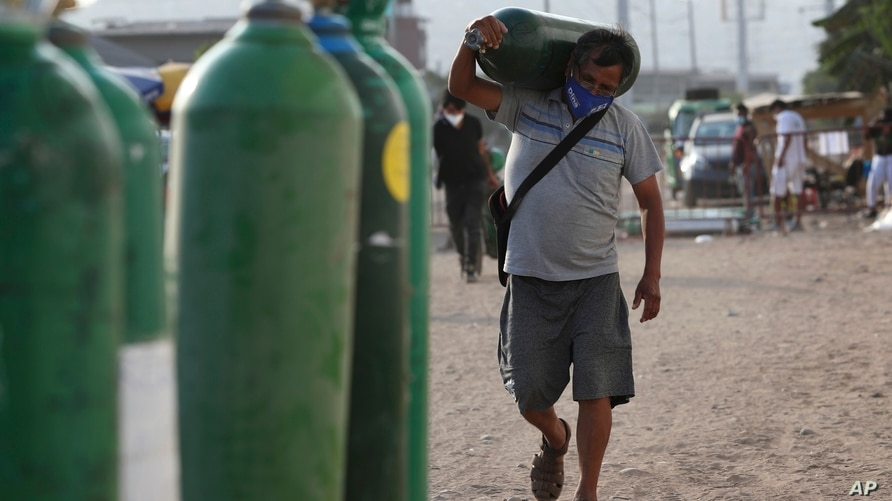 A man carries his empty oxygen tank to be filled in the Villa El Salvador neighborhood, in Lima, Peru, Sunday, April 11, 2021,…