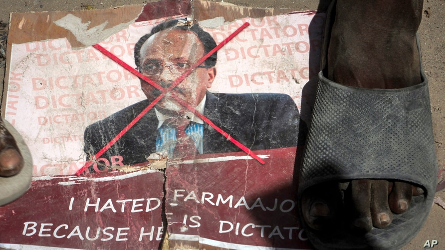 Demonstrators from Somali anti-government opposition groups stand on photographs of the president in the Fagah area of…