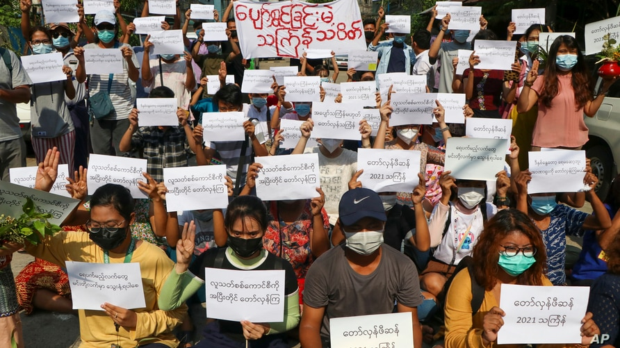 Protesters hold slogans condemning the military government as they mark the Thingyan festival on Tuesday April 13, 2021 in…