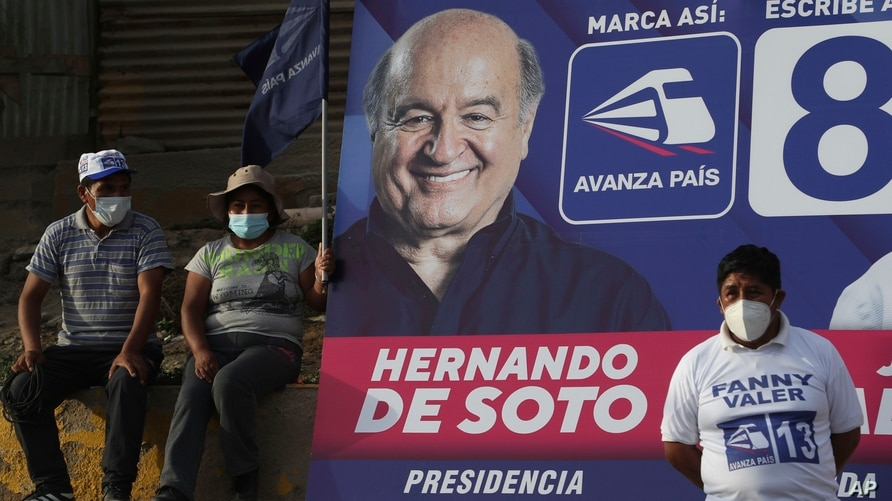 Supporters of Avanza Pais party presidential candidate Hernando De Soto listen to his speech next to a billboard with his image…