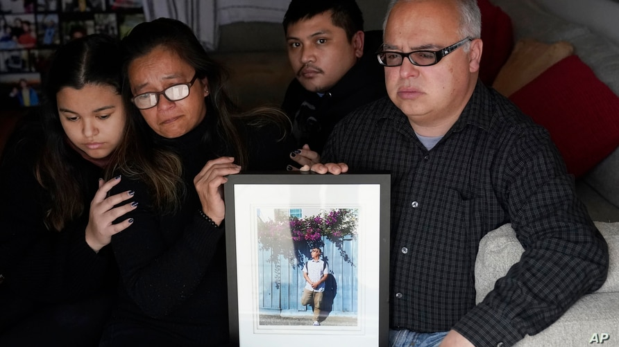 Cassandra Quinto-Collins, second from left, holds a photo of her son, Angelo Quinto, while sitting with daughter Bella Collins,…