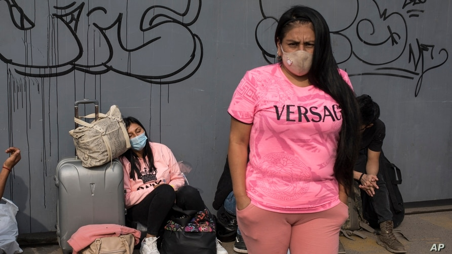 Passengers, wearing protective face masks amid the new coronavirus pandemic, wait outside a long-distance bus terminal, in Lima…