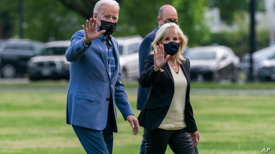 President Joe Biden with first lady Jill Biden wave as they walk on the Ellipse near the White House after spending the weekend…