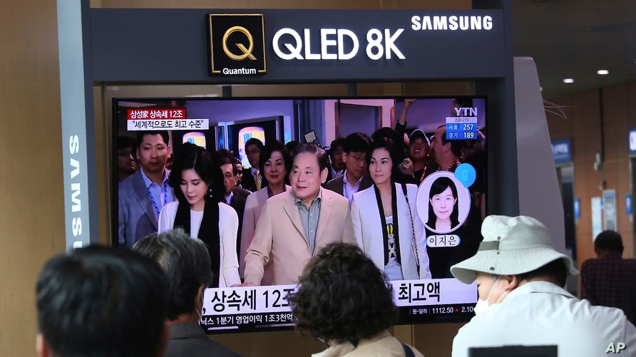 People watch a TV screen showing a file image of the late Samsung Electronics chairman Lee Kun-Hee, center, and his daughters…