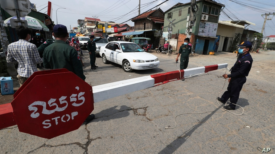 Local police officers stand guard at a blocked street near Phnom Penh International airport in Phnom Penh, Cambodia, Thursday,…