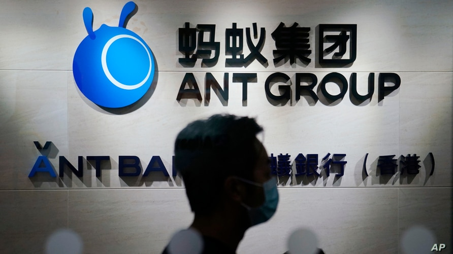 In this Friday, Oct. 23, 2020, photo, an employee walks past a logo of the Ant Group at their office in Hong Kong. The world's…