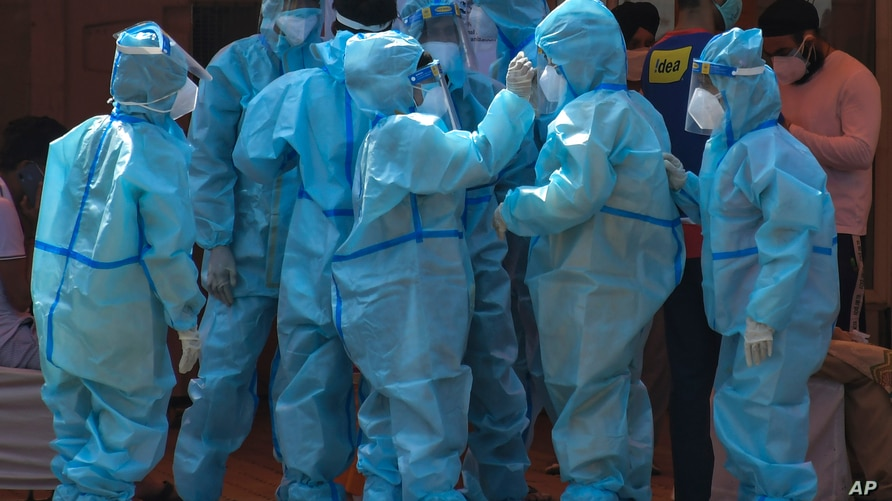 Health workers and volunteers in personal protective suits wait to receive patients outside a COVID-19 hospital that was set up…