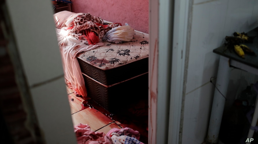 Blood covers the floor and a bed inside a home during a police operation targeting drug traffickers in the Jacarezinho favela…