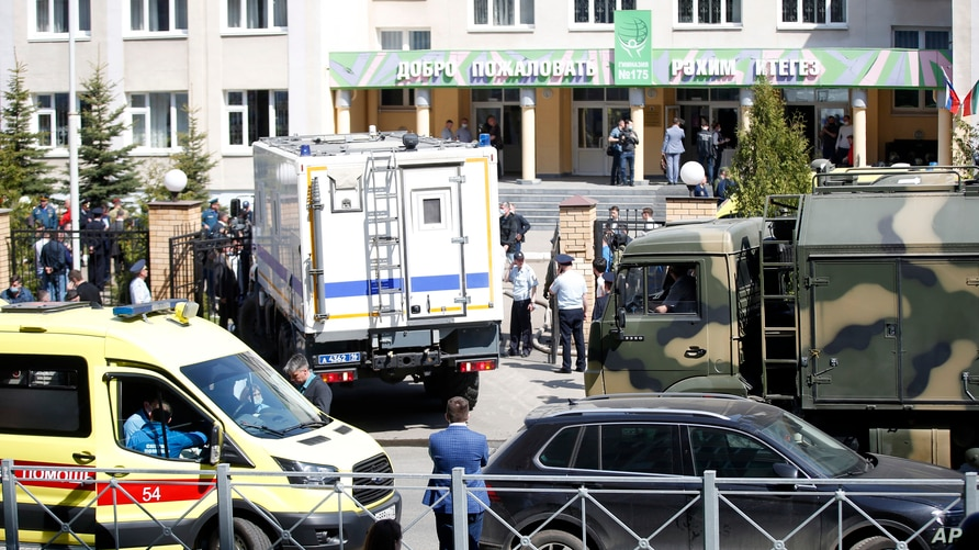 An ambulance and police trucks are parked at a school after a shooting in Kazan, Russia, Tuesday, May 11, 2021. Russian media…