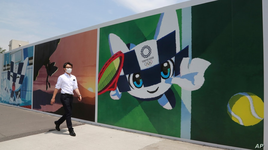 A man walks by posters promoting the Olympic Games planned to start in the summer of 2021, in Tokyo, Monday, May 24, 2021. (AP…