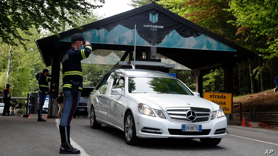 A police officer salutes as a hearse passes by, on the road leading to the Stresa-Mottarone after a cable car of the line…