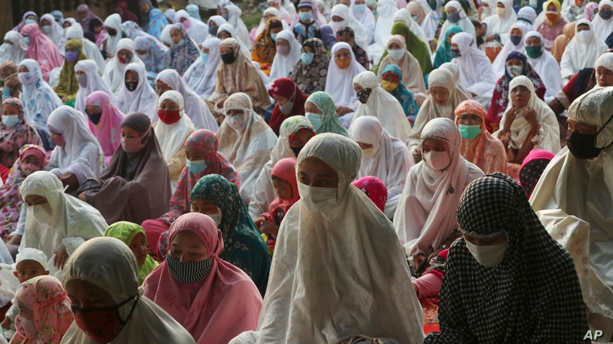 Muslims wear face mask as a precaution against the coronavirus during Eid al-Fitr prayer marking the end of the holy fasting…