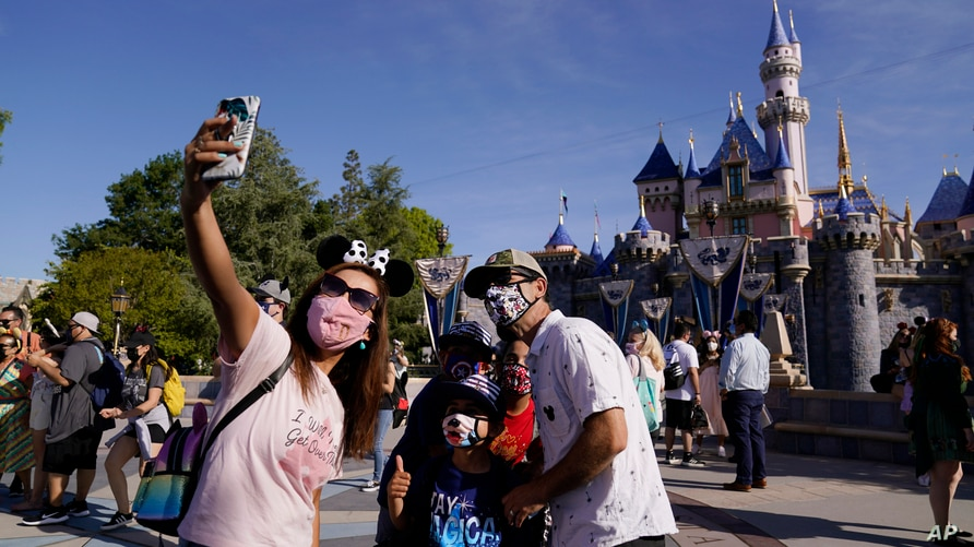 FILE - In this April 30, 2021, file photo, a family takes a photo in front of Sleeping Beauty's Castle at Disneyland in Anaheim…