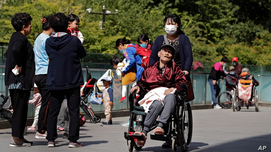 A woman wearing a face mask pushes an elderly man on a wheelchair passes by residents play with their children near a…