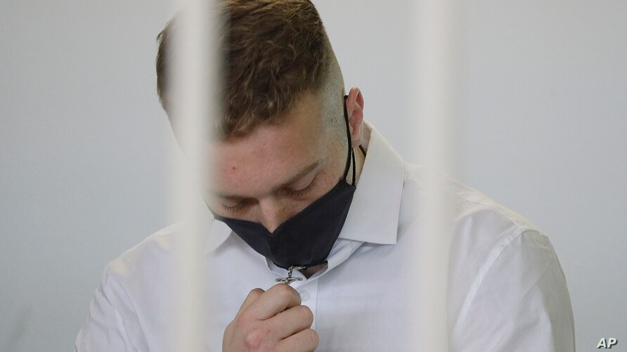 Finnegan Lee Elder touches a crucifix he has around his neck as he wears a face mask to curb the spread of COVID-19 before a…