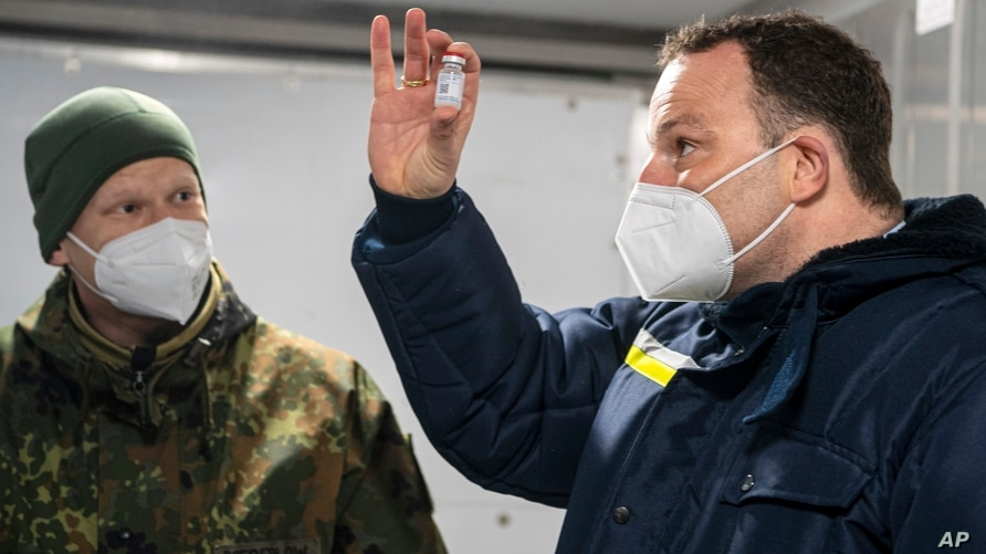 Jens Spahn, Federal Minister of Health, stands with Julian Brederlow, senior staff pharmacist, in a refrigerated container at…