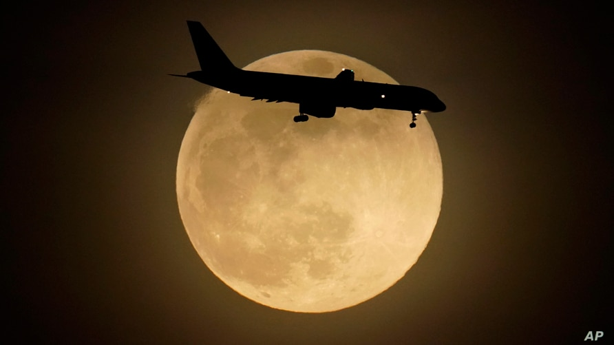 FILE - In this Monday, April 26, 2021 file photo, a jet is silhouetted by the rising moon as it approaches Louisville…