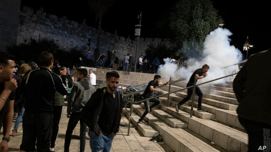 Palestinians react to stun grenades fired by Israeli police to clear the Damascus Gate to the Old City of Jerusalem after…