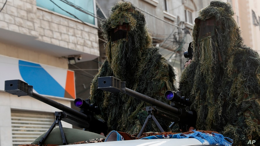 Masked militants from the Izzedine al-Qassam Brigades, a military wing of Hamas, wear camouflage while sitting behind a sniper…