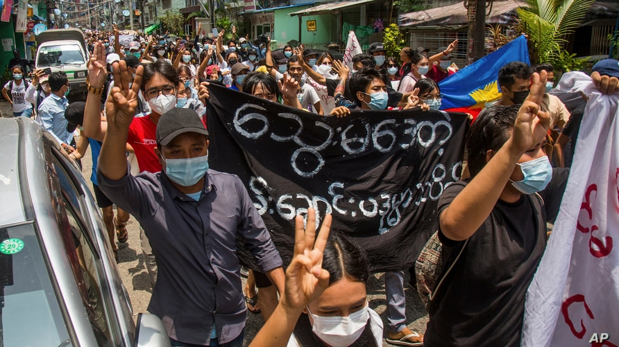 Anti-coup protesters flash the three-finger salute of defiance during a demonstration in Yangon, Myanmar on Tuesday April 27,…