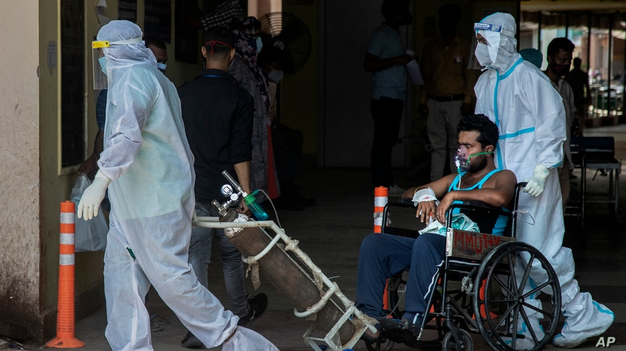 Health workers in protective suits shift a COVID-19 patient at a government hospital in Gauhati, India, Monday, May 24, 2021…