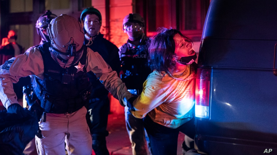 Police arrest a protester as clashes during a march following the presidential election Wednesday, Nov. 4, 2020, in Portland,…