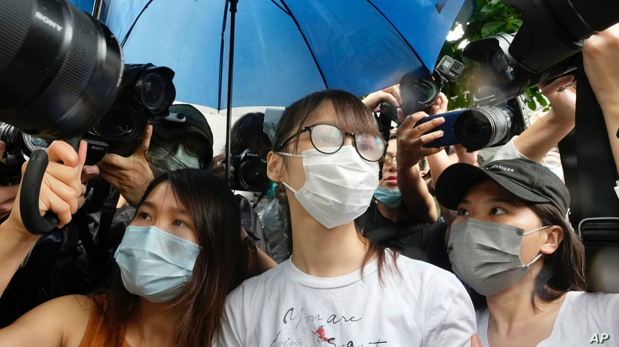 Agnes Chow, center, a prominent pro-democracy activist who was sentenced to jail last year for her role in an unauthorized…