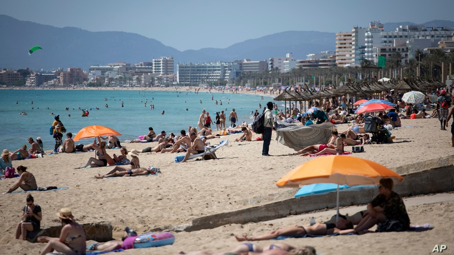 Tourists enjoy the beach at the Spanish Balearic Island of Mallorca, Spain, Monday, June 7, 2021. Spain is jumpstarting its…