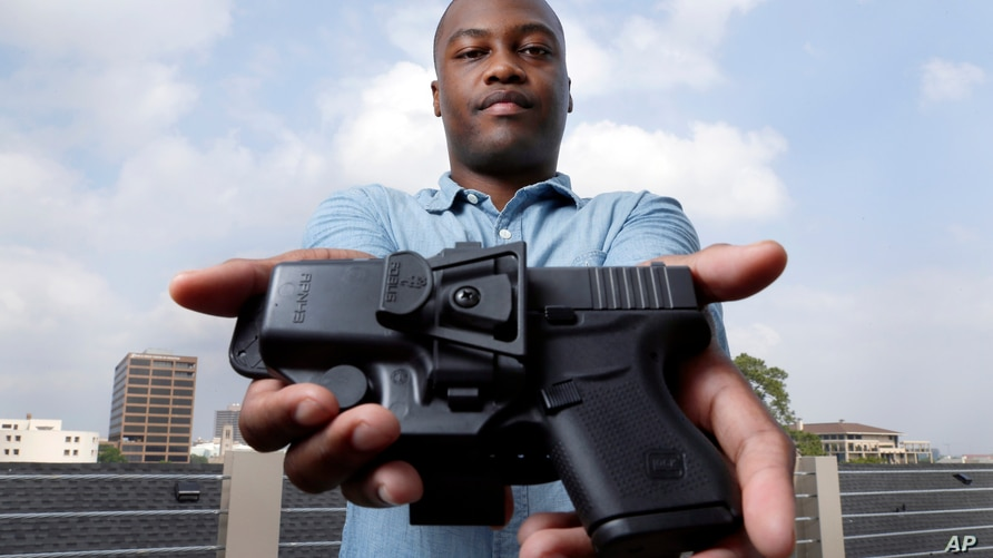 Charles Blain, a new gun owner, poses with his holstered 9mm Glock 43 handgun, Monday, May 3, 2021, on the parking garage of…