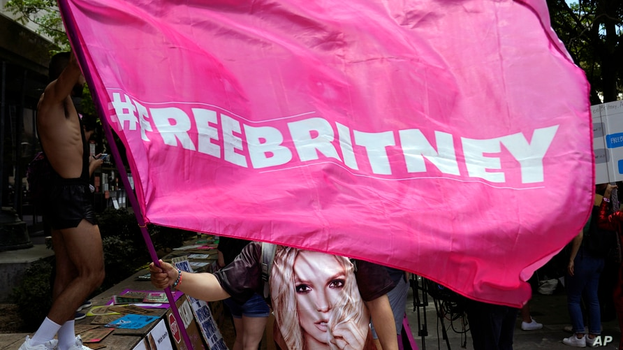 """A Britney Spears supporter waves a """"Free Britney"""" flag outside a court hearing concerning the pop singer's conservatorship at…"""