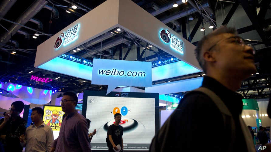 Visitors walk past a display for Chinese microblogging site Weibo at the Global Mobile Internet Conference (GMIC) in Beijing,…