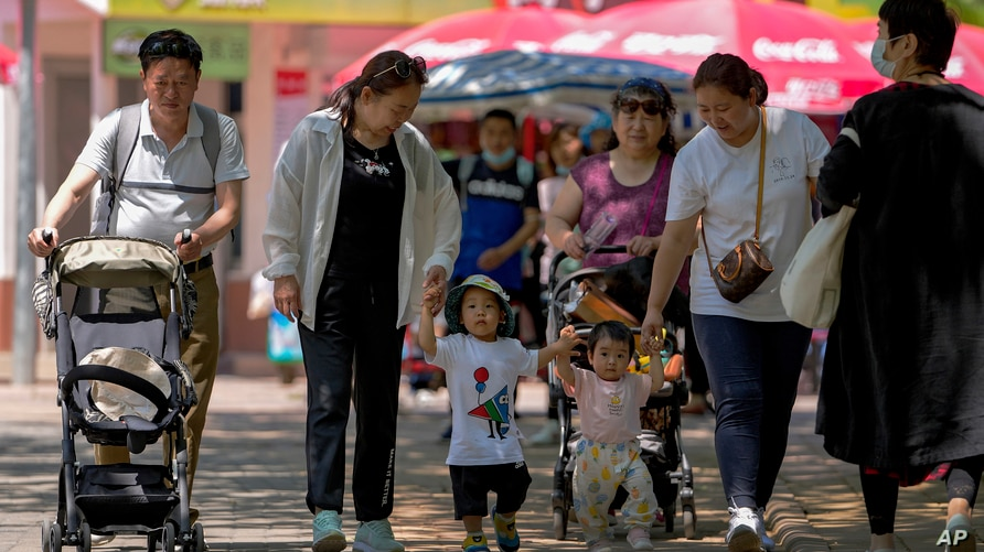 People bring their children to a public park during the International Children's Day in Beijing, Tuesday, June 1, 2021. China's…