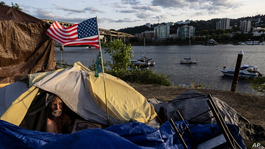 Frank, a homeless man sits in his tent with a river view in Portland, Ore., on Saturday, June 5, 2021. Until a year ago, the…
