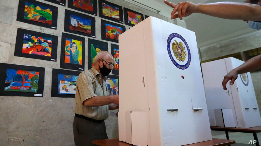 An Armenian man reads his ballot papers at a polling station during a parliamentary election in Yerevan, Armenia, Sunday, June…