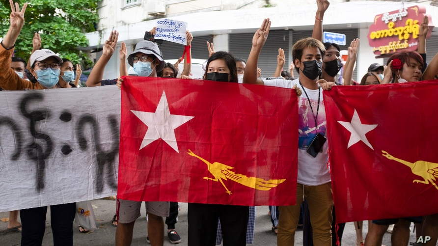 Protesters holding National League for Democracy (NLD) flags raise three-finger salutes during flash protests against the…