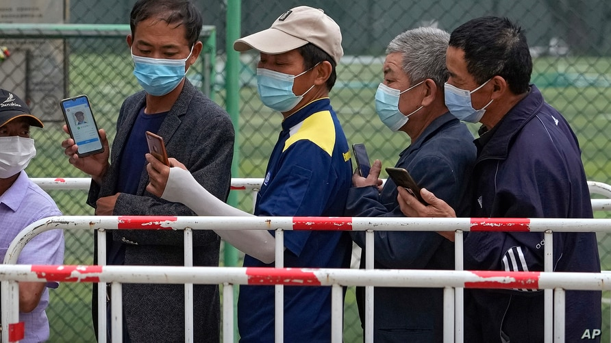 Residents wearing face masks to help curb the spread of the coronavirus look at their smartphones showing health code as they…