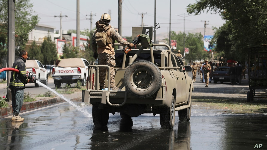 In this June 6, 2021, photo, Afghan security personnel leave the scene of a roadside bomb explosion in Kabul, Afghanistan. The…
