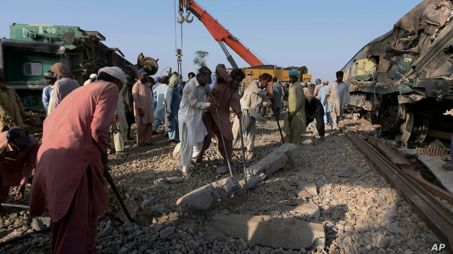 Railway workers rebuild the track at the site of a train collision in the Ghotki district, southern Pakistan, Tuesday, June 8,…
