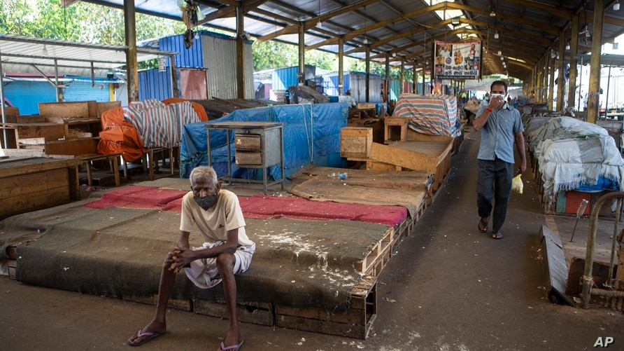 A Sri Lankan man rests in a vegetable market closed to curb the spread of the coronavirus in Colombo, Sri Lanka, Wednesday,…