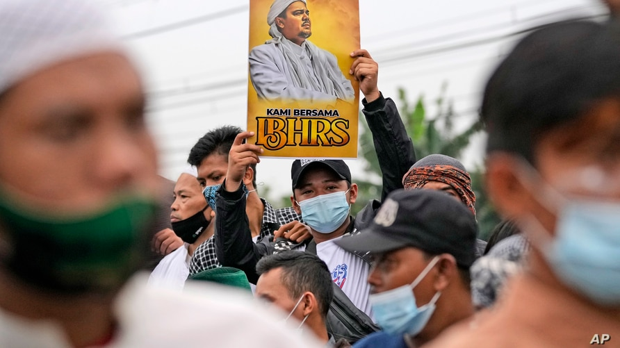 A supporter holds up a poster bearing a portrait of firebrand cleric Rizieq Shihab during a rally near the district court where…
